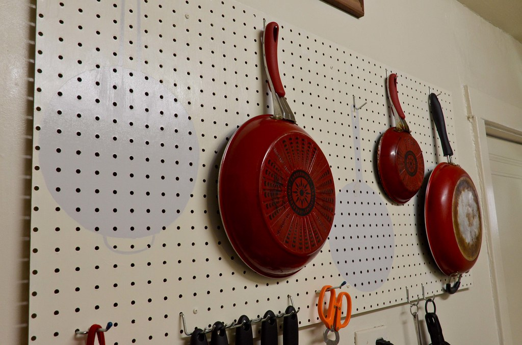 pegboard used to store pots and pans in the kitchen