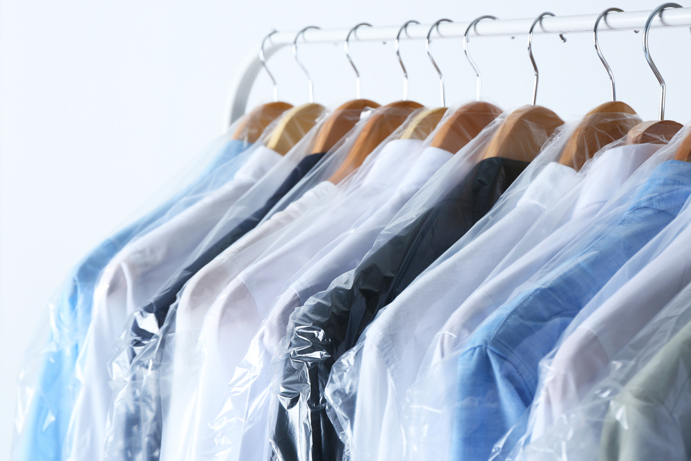 nice shirts hung and covered with plastic for storage