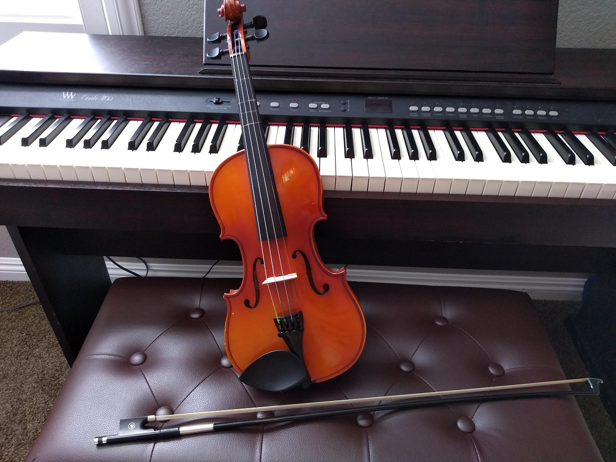 violin sitting against a piano
