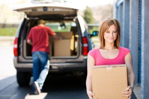 Grand junction woman and man happily moving into their new storage unit with All Secure Storage