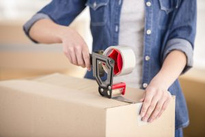 Montrose woman using a tape gun to secure valuables in a moving box to store
