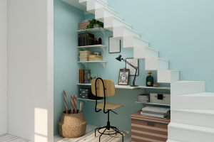 A home office underneath a set of white stairs.