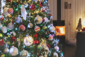 A Christmas tree decorated and set up in a living room with a fire place going. One of the popular stored items in storage units.