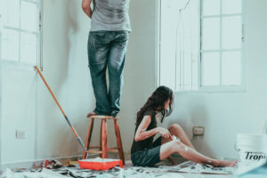 Man and woman painting the walls of their home with newspaper and paint supplies around them.