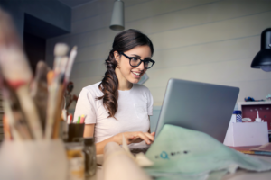 Small business owner woman sitting at desk smiling at laptop with paint brushes and supplies around her.
